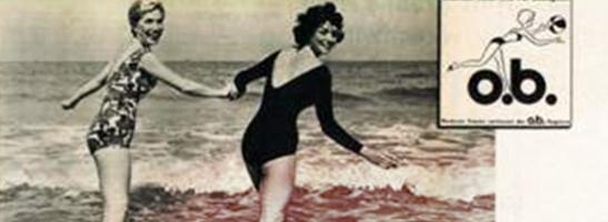 Imagem de duas mulheres em fato de banho, de mãos dadas. A imagem é antiga e ilustra a revolução feminina. Logótipo o.b.® antigo apresentado no canto superior direito.