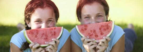 Imagem de duas jovens com uma fatia de melancia em frente do rosto. Esta imagem ilustra como estas sugestões para te sentires bem te ajudarão a fazer aquilo que mais gostas, durante a menstruação.