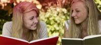 Imagem de duas jovens a ler um livro. A imagem ilustra os vários mitos que estão associados à menstruação.