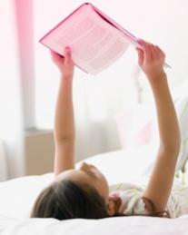 Imagem de uma jovem deitada de costas a ler um artigo. A imagem ilustra que a marca o.b.® tem a resposta para muitas questões e que podes encontrar as respostas no nosso website.