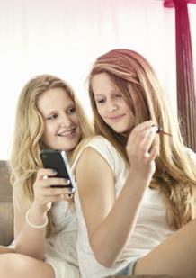 Imagem de duas jovens. Uma está a segurar num telemóvel e a outra a pintar as unhas com verniz. A imagem ilustra que as mudanças que ocorrem no corpo são normais e algo de que podes falar abertamente com as tuas amigas ou os teus pais.